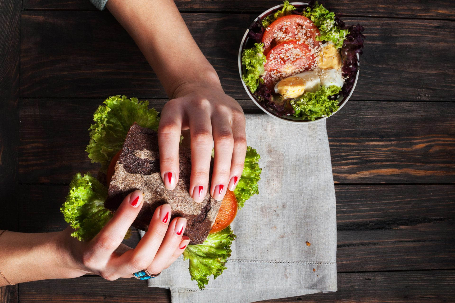 Woman eating tasty and healthy sandwich in hands