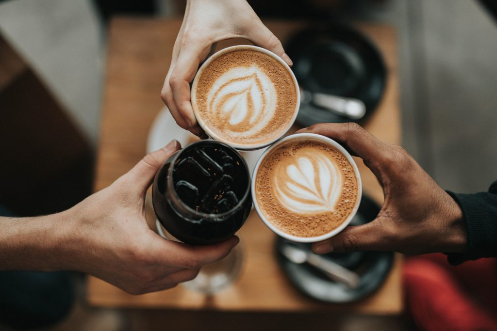 Three people holding cups with coffee