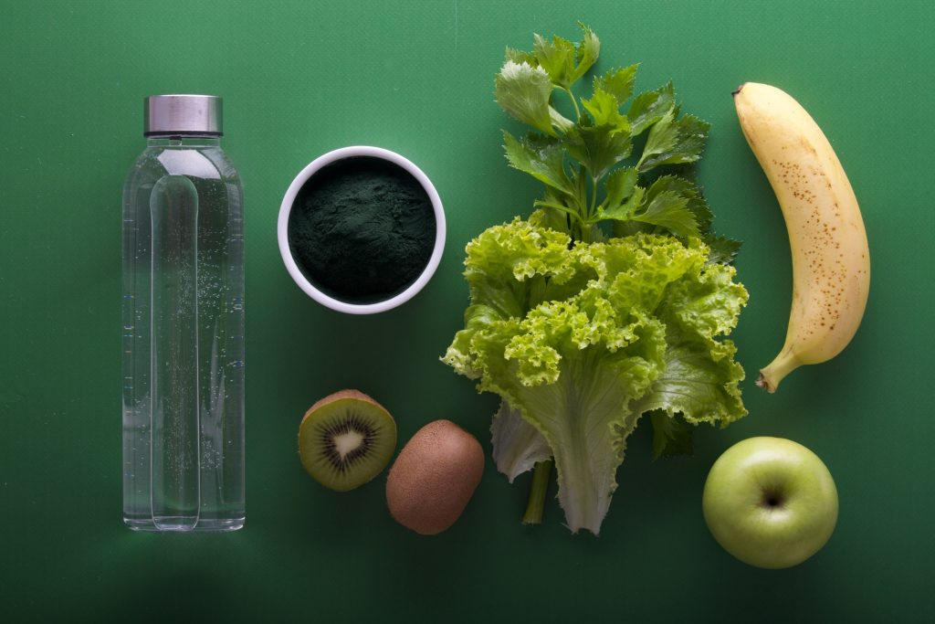 Glass bottle of water and vegetables with fruits on green surface